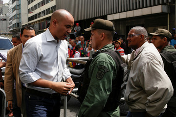 Hector Rodriguez, deputy of Venezuela's United Socialist Party (PSUV), speaks with a Venezuelan National Guard member as he arrives for a session of the National Assembly in Caracas