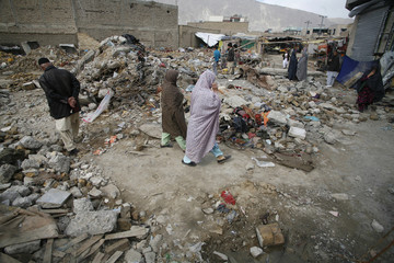 Residents from the Hazara community walk through the rubbles of last month bomb blast in Quetta