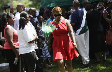 Lesley McSpadden leaves the burial service for her son Michael Brown with a bouquet of flowers at St. Pete's Cemetery in St. Louis, Missouri