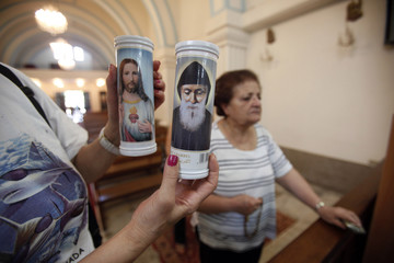 A woman poses with candles with images depicting St. Charbel of Lebanon and Jesus as she prays in front of a copy of the original Shroud of Turin,on display at an Armenian catholic church in Beirut