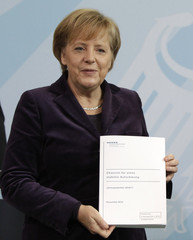 German Chancellor Merkel poses with annual report in Berlin