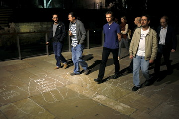 "Men walk over silhouettes of women painted on the floor after a performance titled ""Women in Black"" to protest against gender violence in downtown Malaga"