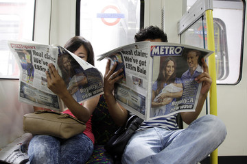 A tube passenger reads a copy of The Sun newspaper featuring a picture of the newborn baby of Catherine, Duchess of Cambridge and Britain's Prince William, on the London underground