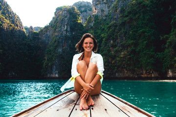 Beautiful happy woman sitting on long tail boat, relaxing, Koh Phi Phi, Thailand
