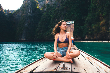 Concept of relaxing vacation on the sea side. Young happy girl relaxing on boat in Thailand