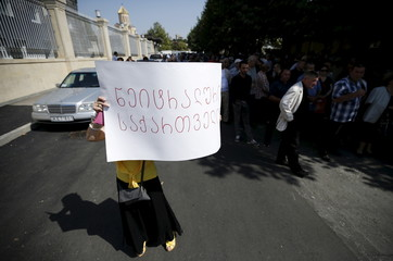 Woman holds a poster during a rally to demand better relations with Russia in Tbilisi