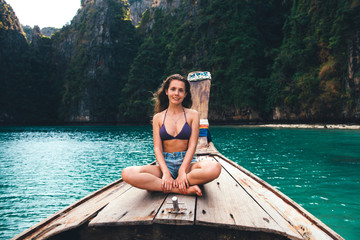 Young girl sitting on long tail boat, relaxing, Koh Phi Phi, Thailand