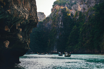 Beautiful mountains at the Phi Phi islands. Touristic boats in the sea in Thailand