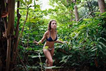 Young beautiful girl in bikini walking in tropical forest. Traveler lost in the jungle forest