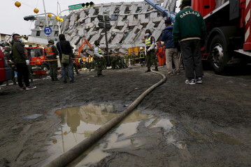 Rescue workers stand near a collapsed building after an earthquake hit Tainan, southern Taiwan