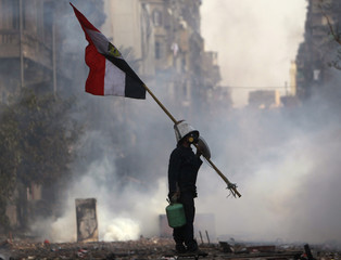 A protester carries an Egyptian national flag as riot police fire tear gas during clashes near Tahrir Square