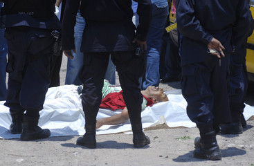 Policemen gather around the slain body of a man at the crime scene in Tegucigalpa