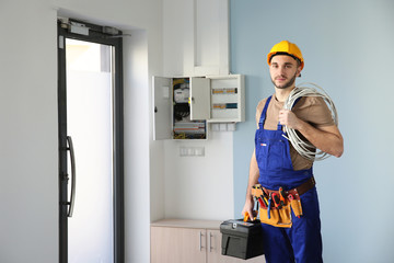 Young electrician with bunch of wires indoors