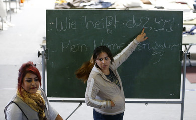A woman points at the blackboard during spontaneously organized English and German lesson for migrants at an improvised temporary shelter in a sports hall in Hanau