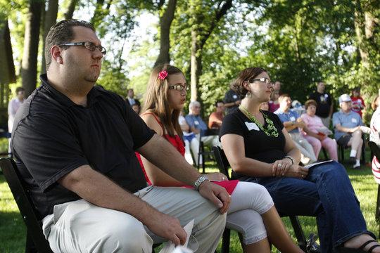Cedar Falls Tea Party leader Saul listens to Republican presidential hopeful Santorum in Iowa