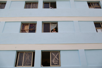 People look from taped windows of a building prior to the arrival of Hurricane Matthew in Siboney
