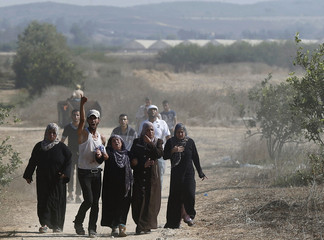 Palestinians react after the removal of the bodies of three militants killed by Israeli forces in Gaza