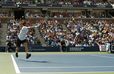 Murray of Britain hits a return to Berdych of the Czech Republic during their men's singles semifinals match at the U.S. Open tennis tournament in New York