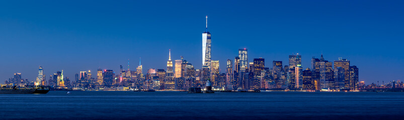 Panoramic view of Lower Manhattan and New York City Harbor with Financial District skyscrapers at twilight