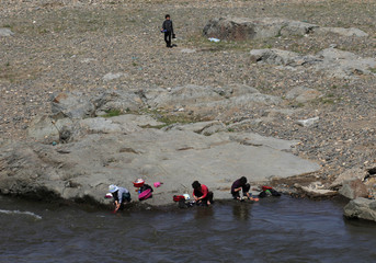 People wash clothes on the banks of a river near the North Korean city of Hyesan, across the Yalu River from the Chinese town of Changbai