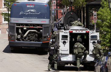 A passenger (top center) walks away from a Greyhound bus with his hands in the air as a SWAT team surround the bus after a call that there might be a bomb on board in Portsmouth