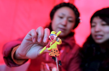 "Folk artist Ma Yueru makes a clay figurine of the ""Monkey King"" also known as ""Sun Wukong"" for visitors at a Spring Festival temple fair on the second day of the Chinese Lunar New Year of the Monkey in Beijing,"