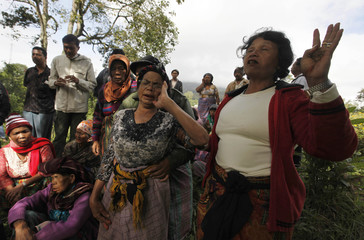 Villagers go into a trance during an ancient ritual as Mount Sinabung volcano spews smoke at Suka Nalu village