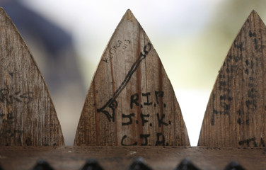 """An inscription reading """"RIP JFK"""" adorns a slat of the wooden picket fence at the top of the """"Grassy Knoll"""" in Dealy Plaza in Dallas"""