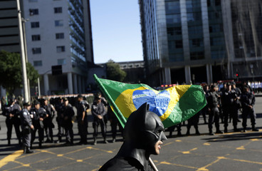An anti-government demonstrator dressed as comic book superhero Batman walks with a Brazilian flag in Rio de Janeiro
