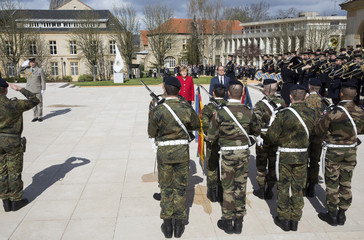 German Chancellor Angela Merkel and French President Francois Hollande review troops as they arrive to attend a joint Franco-German cabinet meeting in Metz
