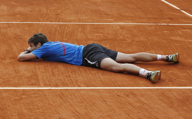 Robredo of Spain lies on the court after defeating Monfils of France in their men's singles match during the French Open tennis tournament in Paris