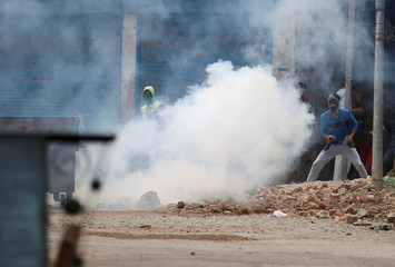 Protesters throw stones amid tear gas smoke fired by Indian police during a protest against the killing of Wani, a separatist militant leader, in Srinagar