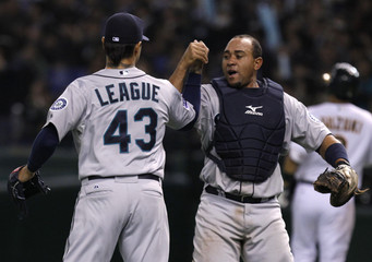 Seattle Mariners' closer pitcher League celebrates with teammate catcher Olivo to win their American League season opening MLB baseball game against the Oakland Athletics in Tokyo