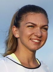 Tennis player Simona Halep of Romania poses for photos after practising yoga during sunrise on the observation deck of the Marina Bay Sands hotel in Singapore