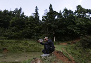 Ethnic Miao man Gun Liangma, 44, fires his gun during shooting practice in Congjiang county