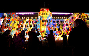 People take pictures of a design projected onto the Museum of Contemporary Art during the opening night of the annual Vivid Sydney light festival in Sydney