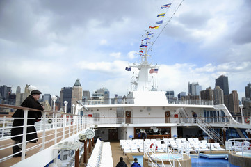 A passenger looks out over the deck of the Azamara Journey cruise ship in New York