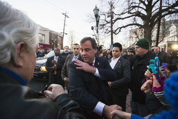 New Jersey Governor Chris Christie brushes lint off his shoulder as he greets residents after departing City Hall in Fort Lee, New Jersey