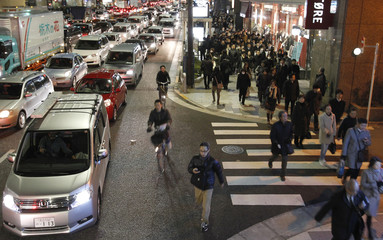 Residents walk between grid locked vehicles on their way home among chaotic traffic in central Tokyo, after an earthquake off the coast of northern Japan