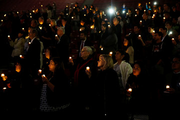 People hold lit candles during a memorial on the one year anniversary of the San Bernardino attack, inside Coussoulis Arena at Cal State University San Bernardino in San Bernardino