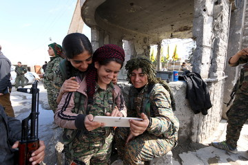 Female fighters from the Democratic Forces of Syria use a tablet in al-Shadadi town, in Hasaka province
