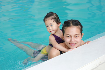 Portrait of mother and little girl in swimming pool.