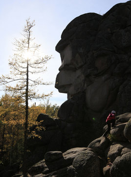 A tourist climbs up near a rock at the Stolby national nature reserve outside Krasnoyarsk