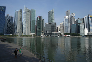 Youth carrying fishing rods pass the Marina Bay overlooking the central business district skyline in Singapore
