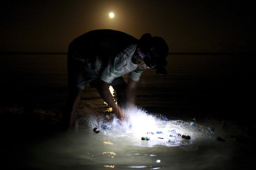 A fisherman uses a headlight while cleaning a fishnet before loading it on his small boat as the moon sets down at a shore in Mogpog town