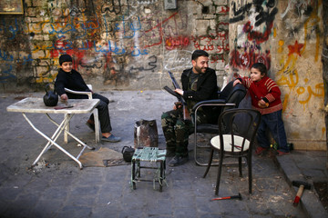 A Free Syrian Army fighter jokes with a child in the old city of Aleppo