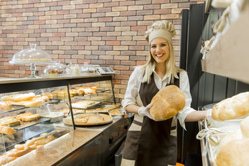 Young woman takes fresh bread from the shelves in a baker shop