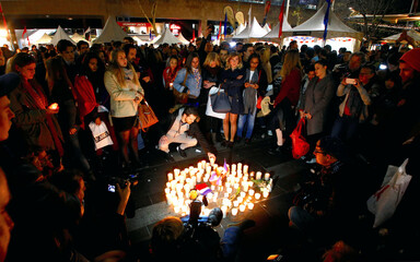 Members of the Australian French community place candles during a vigil in central Sydney