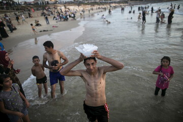 A teen holds a jellyfish over his head on a beach of the Mediterranean in Tel Aviv during Eid al-Fitr