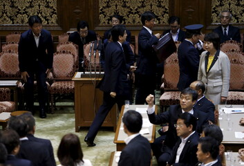 Japan's Prime Minister Shinzo Abe leaves an upper house special committee session on security-related legislation while lawmakers crowd around Konoike, chairman of the upper house special committee on security, at the parliament in Tokyo